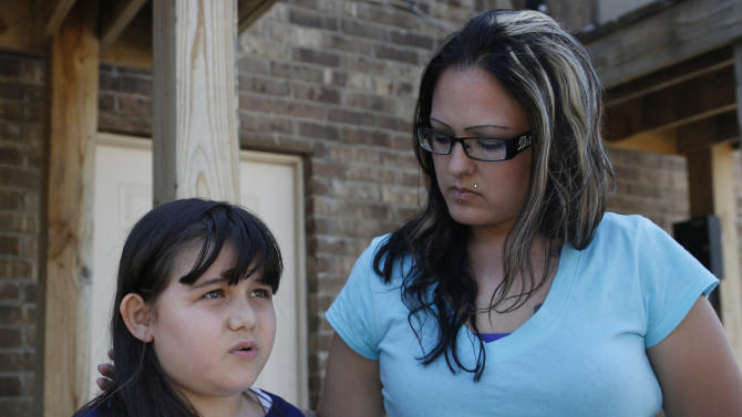 Jazmin Rodriguez, left, answers questions during an interview as her mother, LaTisha Garcia, right, looks on, in Moore, Okla., Thursday, May 23, 2013. Garcia carried her injured daughter away from a school that was hit by a tornado on Monday. (AP Photo/Sue Ogrocki)
