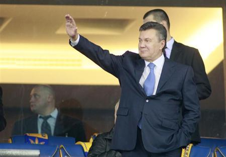 Ukrainian President Viktor Yanukovich waves before the 2014 World Cup qualifying soccer match between Ukraine and England at the Olympic stadium in Kiev