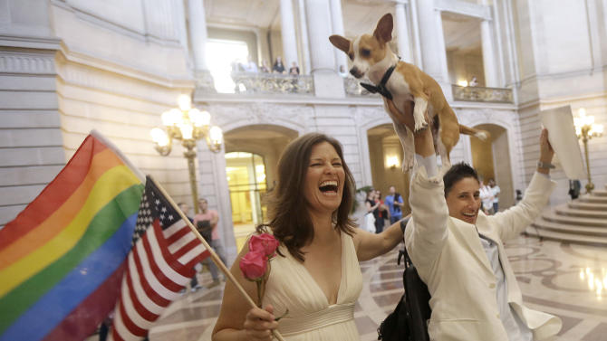"""Jen Rainin, left, laughs as her wife Frances holds up their dog Punum after they were married at City Hall in San Francisco, Friday, June 28, 2013. A three-judge panel of the 9th U.S. Circuit Court of Appeals issued a brief order Friday afternoon dissolving, """"effective immediately,"""" a stay it imposed on gay marriages while the lawsuit challenging the ban advanced through the courts. (AP Photo/Jeff Chiu)"""