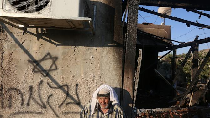 """A Palestinian man stands next to graffiti reading in Hebrew """"Revenge"""", after a house was set on fire in the West Bank village of Duma on July 31, 2015"""
