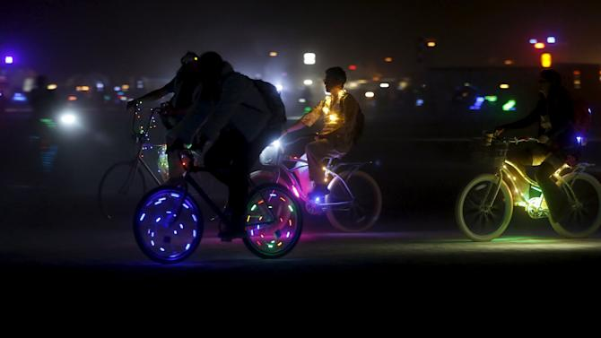 """Participants illuminate their bikes for travel at night on the Playa during the Burning Man 2015 """"Carnival of Mirrors"""" arts and music festival in the Black Rock Desert of Nevada"""