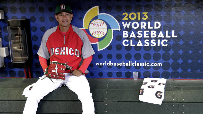 Mexico's Eduardo Arredondo watches batting practice from the dugout prior to a World Baseball Classic baseball game against Canada, Saturday, March 9, 2013, in Phoenix. (AP Photo/Matt York)