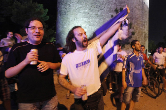 Greek fans celebrate in downtown of Thessaloniki on Sunday June 17, 2012. A defensive Greece held off a nearly nonstop Russian attack on Saturday, putting the 2004 champions into the European Championship quarterfinals and eliminating Russia with a 1-0 victory. (AP Photo/Dimitri Messinis)