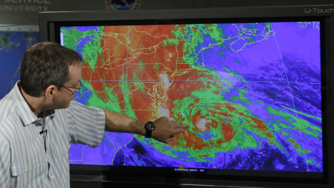 James Franklin, Branch Chief of Hurricane  Forecast Operations, points to a weather satellite map as he talks to a reporter at the National Hurricane Center in Miami, Thursday, April 4, 2013. The National Weather Service is now changing how it issues hurricane and tropical storm warnings. Starting June 1, watches and warning will be issued for storms that threaten life and property even after they are no longer hurricanes or tropical storms. (AP Photo/Alan Diaz)