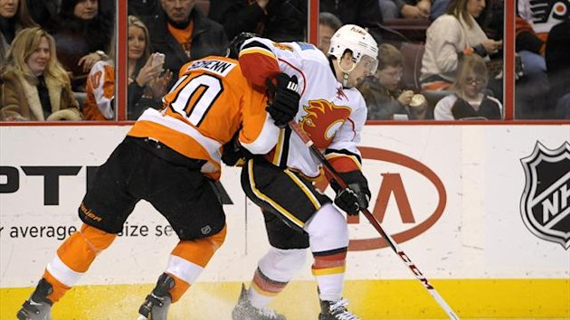 Calgary Flames defenseman Kris Russell (4) moves the puck past Philadelphia Flyers center Brayden Schenn (10) during the third period at Wells Fargo Center (Reuters)