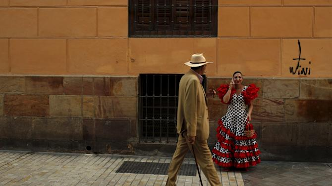 A woman wearing a traditional Sevillana dress talks on her phone during a hot summer day in downtown Malaga