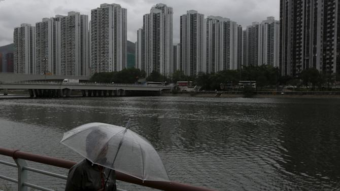 A passer-by walks along a riverside as City One Shatin residential precinct is seen at background in Hong Kong