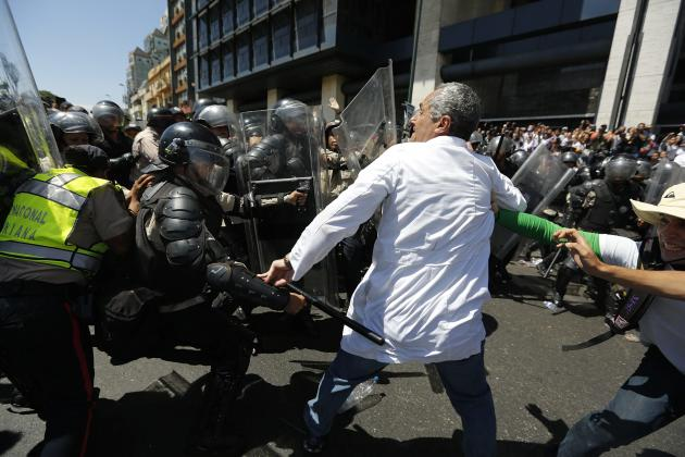 National policemen scuffle with anti-government doctor during a march to demand medical supplies for hospitals in Caracas