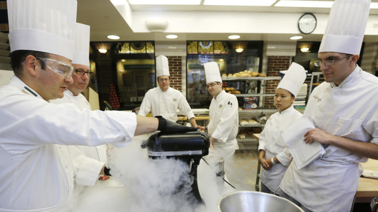 In this image taken on Friday, Sept. 14, 2012, Chef Francisco Migoya, left, demonstrates how to make strawberry sorbet by applying liquid nitrogen to a puree mixture at the Culinary Institute of America in Hyde Park, N.Y. This esteemed cooking school north of New York City is dramatically pumping up science instruction, saying that tomorrow's chefs will need more technical know-how in the age of molecular gastronomy and sous-vide. (AP Photo/Mike Groll)