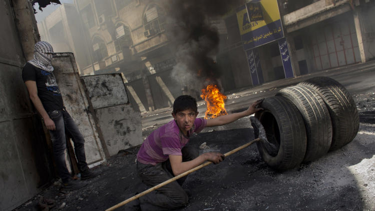 A Palestinian youth prepares to set tires on fire Wednesday, April 3, 2013, during a protest against Israeli forces in the West Bank city of Hebron after the death of Palestinian prisoner Maysara Abu Hamdiyeh at an Israeli jail. Palestinian prisoners have been rioting and hunger striking since 64-year-old Abu Hamdiyeh died of throat cancer on Tuesday. The Palestinians have blamed Israel for the man's death, saying he was not given proper medical care. Abu Hamdiyeh had been serving a life sentence for his role in a foiled attempt to bomb a busy cafe in Jerusalem in 2002. (AP Photo/Bernat Armangue)