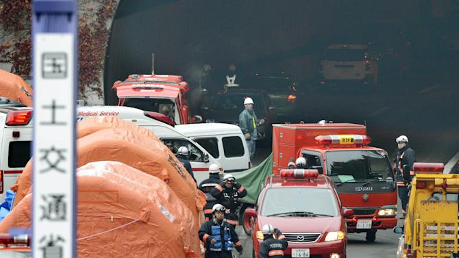 """Firefighters work at the exit of the Sasago Tunnel on the Chuo Expressway in Otsuki, Yamanashi Prefecture, central Japan, Monday morning, Dec. 3, 2012. Concrete ceiling slabs fell onto moving vehicles deep inside the tunnel Sunday, and authorities confirmed nine deaths before suspending rescue work Monday while the roof was being reinforced to prevent more collapses. The sign attached to a mobile lighting pole, left, reads """"Land and Transport Ministry."""" (AP Photo/Kyodo News) JAPAN OUT, MANDATORY CREDIT, NO LICENSING IN CHINA, FRANCE, HONG KONG, JAPAN AND SOUTH KOREA"""