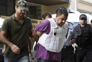 Police officers escort a man, a supporter of the Golden Dawn group and who admitted to the killing of rapper Fissas, into a prosecutor's office in Piraeus