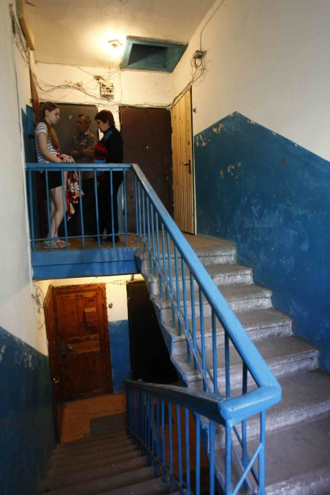 Residents talk in the stairwell of a building where suspected militants were killed during a shootout, in Orekhovo-Zuyevo
