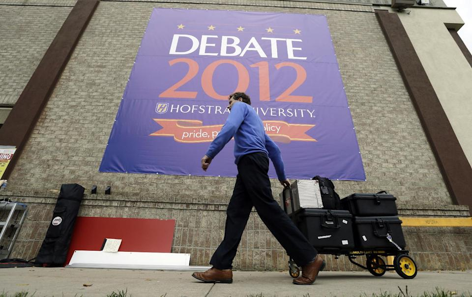 A member of the media moves equipment outside the media filing center in preparation for Tuesday's presidential debate between President Barack Obama and Republican presidential candidate, former Massachusetts Gov. Mitt Romney, Monday, Oct. 15, 2012, at Hofstra University in Hempstead, N.Y. (AP Photo/Charlie Neibergall)