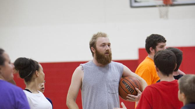 Justin Underwood, center, a reading and language arts teacher at Southside K-8 School in War, W.Va., prepares to play a students versus teachers basketball game after school on Tuesday, May 7, 2013. The school located in McDowell County, an area overwhelmed with poverty, unemployment, drug abuse, and teacher shortages, provides after school access to computers, tutoring, recreation and a meal. McDowell County on Wednesday was expected to win approval to expand its role to include social services in a county that faces deep economic challenges. The project, called Reconnecting McDowell, brings together medical professionals, telecommunications firms and a teachers' union. (AP Photo/Randy Snyder)