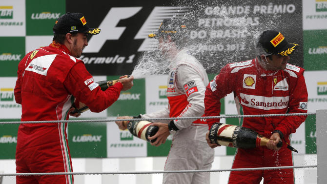 Ferrari driver Fernando Alonso. left, of Spain, sprays champagne on teammate Felipe Massa, of Brazil at the podium of the Formula One Brazilian Grand Prix at Interlagos race track in Sao Paulo, Brazil, Sunday, Nov. 25, 2012. Red Bull driver Sebastian Vettel, of Germany, overcame a first-lap crash to clinch his third straight Formula One championship title on Sunday, finishing sixth in an incident-filled Brazilian Grand Prix won by Jenson Button under pouring rain. (AP Photo/Victor R. Caivano)