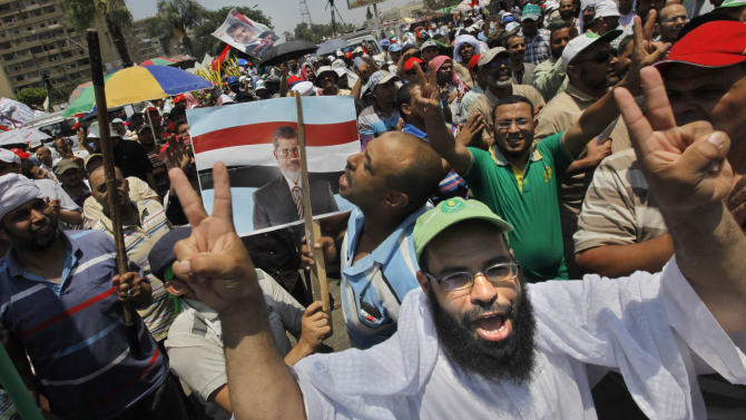 Supporters of Egypt's Islamist President Mohammed Morsi flash v-signs and shout anti-opposition slogans as they hold a poster of the president at a public square outside the Rabia el-Adawiya mosque near the presidential palace in Cairo, Saturday, June 29, 2013. Thousands of supporters and opponents of Egypt's embattled Islamist president held rival sit-ins in separate parts of Cairo Saturday on the eve of opposition-led mass protests aimed at forcing Mohammed Morsi from power. (AP Photo/Amr Nabil)