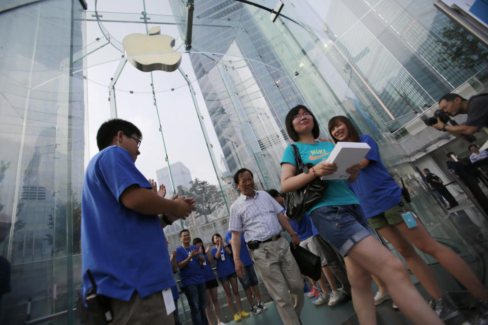 Customers walk out after purchasing Apple's new iPad tablet computers at an Apple Store Friday July 20, 2012 in Shanghai, China. (AP Photo/Eugene Hoshiko)