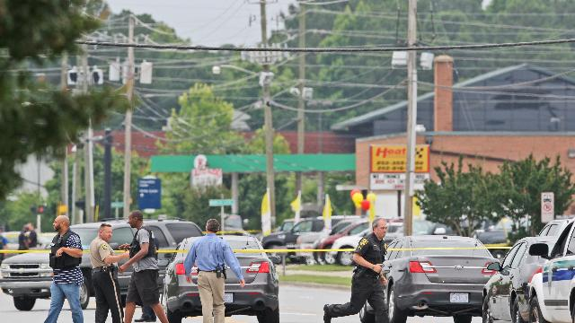 Police investigate the scene of a shooting on Friday, June 21, 2013 in Greenville, N.C. A man armed with a shotgun wounded one person at a North Carolina law firm Friday before crossing a busy street and entering a Wal-Mart, where he shot three more people before officers subdued him, police said. Greenville Police Chief Hassan Aden said the suspect was shot by officers at the entrance of the store. He didn't have the conditions of those shot and didn't have a motive. (AP Photo/The Daily Reflector, Aileen Devlin)