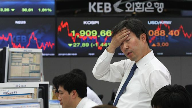 A currency trader reacts in front of screens showing the Korea Composite Stock Price Index (KOSPI), center, and foreign exchange rate, right, at the foreign exchange dealing room of the Korea Exchange Bank headquarters in Seoul, South Korea, Thursday, Nov. 8, 2012. South Korea's Kospi dropped 1.19 percent at 1,914.43. (AP Photo/Ahn Young-joon)