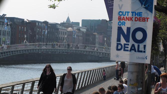 Dubliners bask in the sunshine on the River Liffey as an anti-EU poster advises voters to reject the European Union's fiscal treaty in Dublin, Ireland, on Friday, May 25, 2012. Ireland's May 31 referendum represents the only popular test of public support for the treaty, which is designed to restrict the ability of eurozone members to run up deficits. Prime Minister Enda Kenny made a televised appeal to his nation Sunday to support the treaty, arguing it would reassure the world that Ireland is serious about tackling its deficits and staying in the euro. (AP Photo/Shawn Pogatchnik)