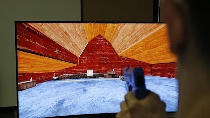 In this May 29, 2015, photo, Vice President of Game Development Baron Giuffria demonstrates a first person skill based gambling game prototype by G2 Game Design in Las Vegas. The player uses a gun to shoot much like a video game. (AP Photo/John Locher)