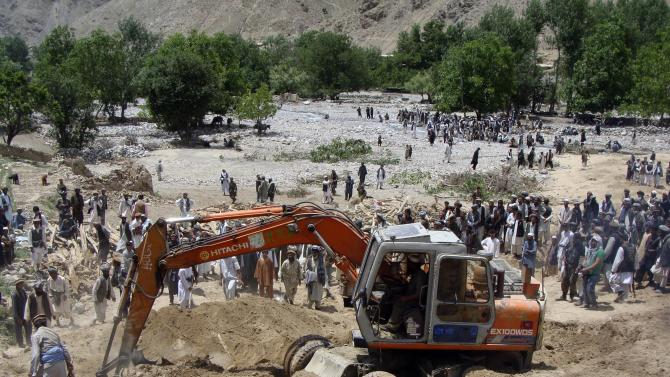 A man, right, reacts as people search for victims of Monday's earthquake in Baghlan, north of Kabul, Afghanistan on Tuesday, June 12, 2012. Scores of people are feared entombed under tons of rock and stone that buried a village in a landslide after two earthquakes in northern Afghanistan, authorities said Tuesday. A single bulldozer worked to uncover the bodies of those killed in Monday's landslide after the earthquakes struck the Hindu Kush region, but villagers fear there will be no survivors. (AP Photo/Jawed Bashara)
