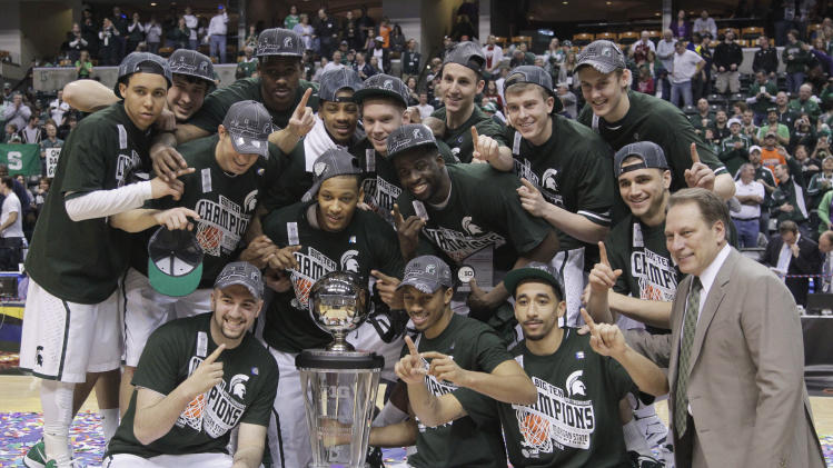 Michigan State players gather around the Big Ten men's tournament trophy for photos after an NCAA college basketball game against Ohio State in the tourney final, in Indianapolis on Sunday, March 11, 2012. Michigan State won 68-64. (AP Photo/Michael Conroy)