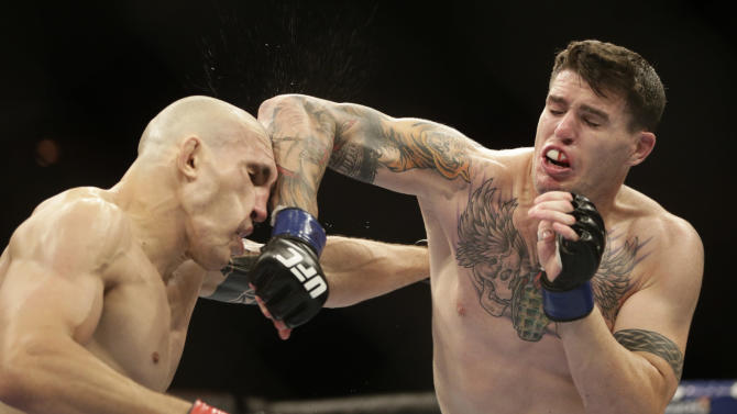 Luiz Cane lands an elbow to Chris Camozzi's head during their middleweight fight at UFC 153. (AP)