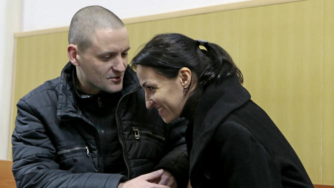 Russian opposition leader Sergei Udaltsov, left, talks with his wife Anastasya in a courtroom in Moscow, Russia, Saturday, Feb. 9, 2013. Udaltsov, a top Russian opposition figure, has been placed under house arrest for two months, a move that also bans him from using most forms of communication, including the Internet, telephone and mail. A Moscow court imposed the restrictions Saturday after prosecutors complained he had violated a previous agreement not to leave Moscow. (AP Photo/Mikhail Metzel)