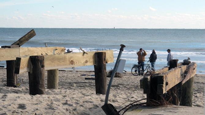 This Nov. 1, 2012 photo shows teens on the beach at Point Pleasant Beach, N.J., next to pilings that used to support part of a boardwalk that was washed away by Superstorm Sandy. Coastal towns are racing to repair their boardwalks in time for next summer. (AP Photo/Wayne Parry)