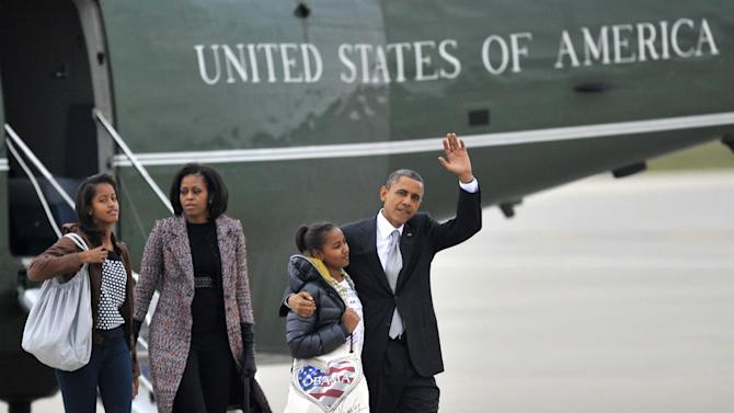 President Barack Obama waves as he walks off Marine One with daughters Sasha, second from right,  Malia, left, and first lady Michelle Obama before leaving O'Hare International Airport in Chicago, Wednesday, Nov. 7, 2012. (AP Photo/Paul Beaty)