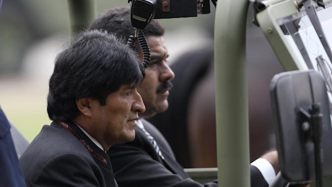 Bolivia's President Evo Morales rides along with Venezuela's acting President Nicolas Maduro as Maduro in a military vehicle  leading a procession carrying the coffin containing the remains of Venezuela's late President Hugo Chavez  in Caracas, Venezuela, Friday, March 15, 2013. Chavez's body is being transferred Friday from the military academy where it has been lying in state to the military museum that will serve as final resting place. (AP Photo/Fernando Llano)