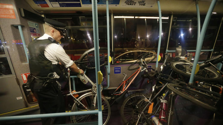 An officer loads arrested cyclist's bicycles after a Critical Mass bike protest outside the Olympic Park during the 2012 Summer Olympics Opening Ceremony, Friday, July 27, 2012, in London. (AP Photo/Matt Rourke)