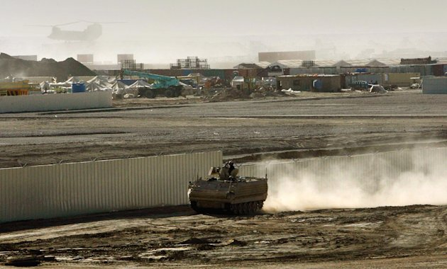 FILE- A British armored vehicle patrols on the periphery of the camp Bastion in southern Afghanistan, in this Wednesday, Jan. 10, 2007 file photo. The Taliban claimed responsibility on Saturday Sept 15 2012 for an attack against the sprawling British base in southern Afghanistan that killed two U.S. Marines and wounded several other troops, saying it was to avenge an anti-Islamic film which insulted the Prophet Muhammad and also because Britain&#39;s Prince Harry is serving there.The camp Bastion, which is the middle of the Afghanistan desert, locally called Dasht-e-Margo or &#39;the desert of death&#39; houses some 3,500 British servicemen and provides logistic supports to all the troops for their various operations in Southern Afghan. (AP Photo/Manish Swarup, File)