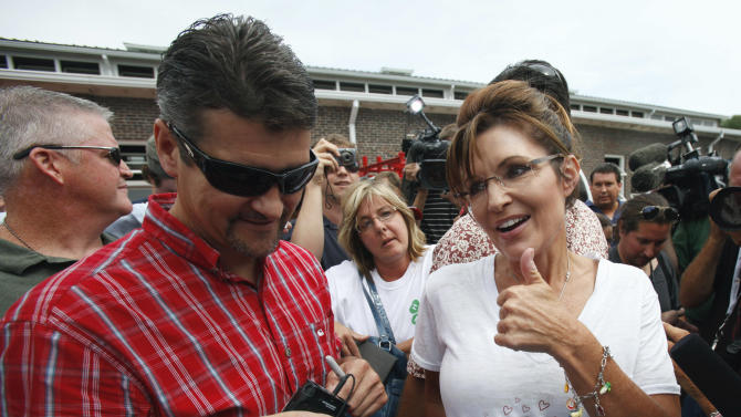 Former Alaska Gov. Sarah Palin and husband Todd, greet fair goers during a visit to the Iowa State Fair in Des Moines, Iowa,  Friday, Aug. 12, 2011. (AP Photo/Charlie Neibergall)