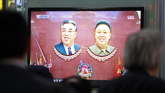 People watch TV news program showing portraits of North Korea founder late Kim Il Sung, left, and his son leader late Kim Jong Il at Seoul Railway Station in Seoul, South Korea, Monday, April 15, 2013. Oblivious to international tensions over a possible North Korean missile launch, Pyongyang residents spilled into the streets Monday to celebrate a major national holiday, the birthday of their first leader, Kim Il Sung. (AP Photo/Ahn Young-joon)