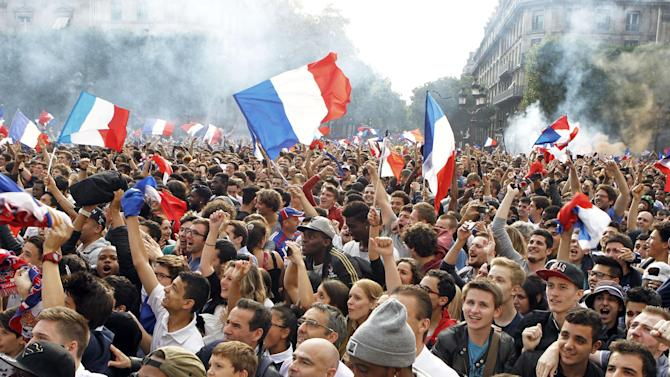 French soccer fans celebrate after France scored the first goal, as they watch the World Cup soccer match between France and Nigeria being shown live on a giant screen, in front of Paris City Hall, Monday June 30, 2014. France won the match 2-0, played at the Estadio Nacional stadium in Brasilia, Brazil.(AP Photo/Remy de la Mauviniere)