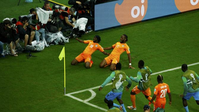 Ivory Coast's Gervinho and Drogba celebrate their goal against Japan during their 2014 World Cup Group C soccer match at the Pernambuco arena in Recife