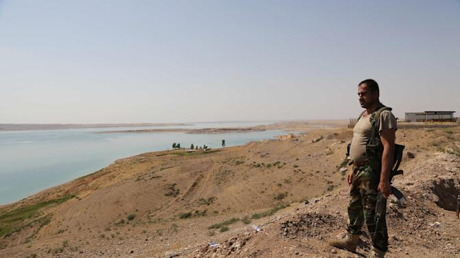 A Kurdish peshmerga fighter stands guard near the Mosul Dam at the town of Chamibarakat outside Mosul, Iraq, Sunday, Aug. 17, 2014. Kurdish forces took over parts of the largest dam in Iraq on Sunday less than two weeks after it was captured by the Islamic State extremist group, Kurdish security officials said, as U.S. and Iraqi planes aided their advance by bombing militant targets near the facility. (AP Photo/Khalid Mohammed)