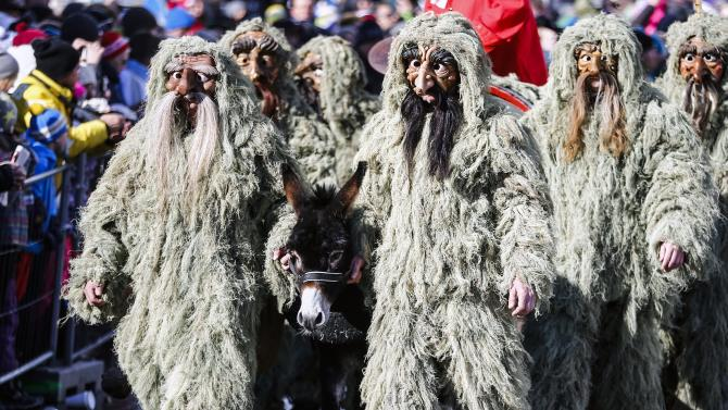 Men in costumes and traditional masks take part in the Schleicherlaufen festival in the western Austrian town of Telfs