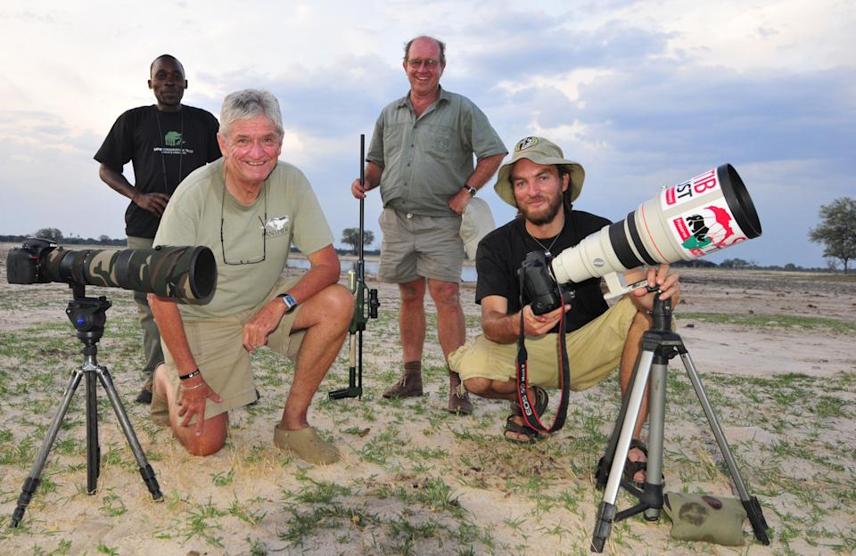 In this photo taken Nov. 9,  2014 photographer Brent Stapelkamp, front right,  with colleagues in the Hwange National Park, Zimbabwe. Stapelkamp, a...