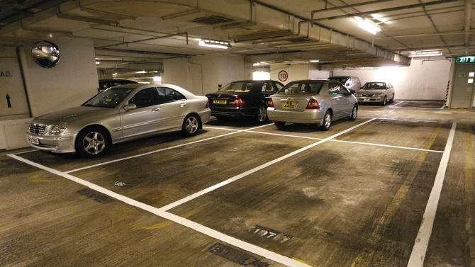 Cars are parked near empty spots at a residential building in Hong Kong Tuesday, Nov. 27, 2012. Investors looking for new areas to park their cash in Hong Kong are driving up prices for parking spaces, sparking fears of a bubble in the Asian financial center. Prices for parking spots in Hong Kong are nearing historic highs, the side effect of government curbs to cool the housing market amid worries of overheating following the latest round of economic stimulus in the U.S. (AP Photo/Vincent Yu)