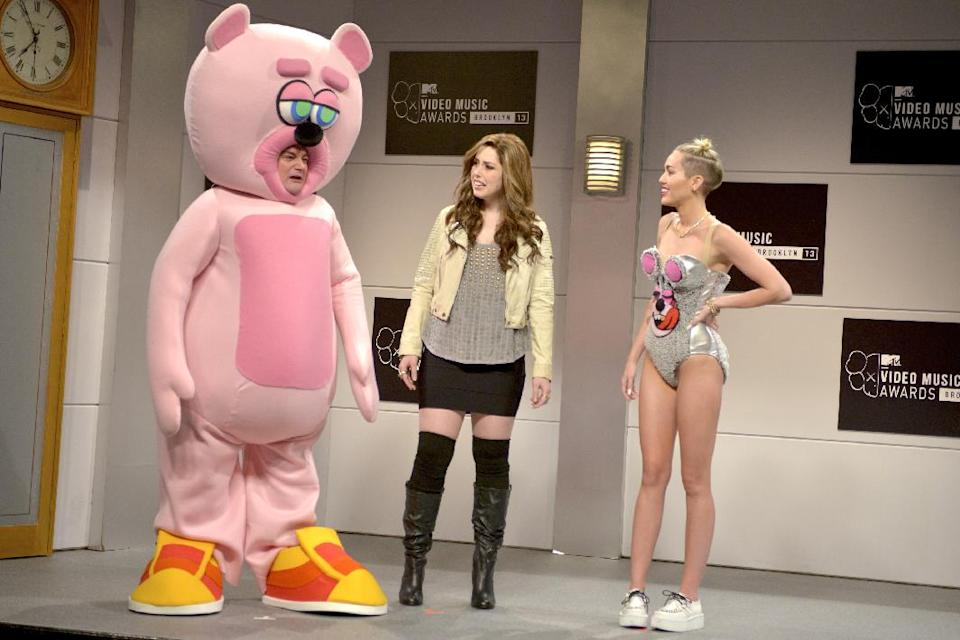 "This Oct. 5, 2013 photo released by NBC shows, from left, Bobby Moynihan, Vanessa Bayer and guest host Miley Cyrus in a scene from the late-night comedy series ""Saturday Night Live,"" in New York. (AP Photo/NBC, Dana Edelson)"