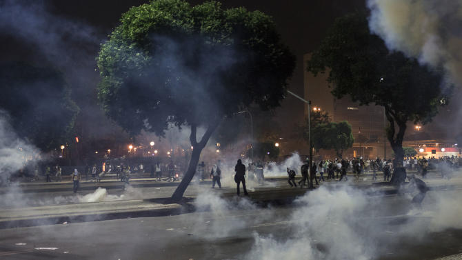 People run from tear gas during a protest in Rio de Janeiro, Brazil, Thursday, June 20, 2013. More than half a million Brazilians poured into the streets of at least 80 Brazilian cities Thursday in demonstrations that saw violent clashes and renewed calls for an end to government corruption and demands for better public services. Riot police battled protesters in at least five cities, with some of the most intense clashes happening in Rio de Janeiro, where an estimated 300,000 demonstrators swarmed into the seaside city's central area. (AP Photo/Felipe Dana)