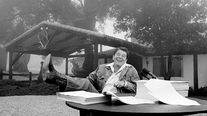 FILE - In this Aug. 14, 1981, file photo, President Ronald Reagan shows his boot following the signing of his tax bill at his California vacation home, Rancho del Cielo, near Santa Barbara, Ca. Reagan might as well be sitting in on the troubled debt talks of 2011, so frequently is his memory invoked by both sides. But for vastly different reasons. Conservative Republicans praise the 40th president's steely advocacy for smaller government and lower taxes. President Barack Obama and his Democratic allies praise Reagan because, they say, he was the sublime compromiser, willing to work with Democrats to forge landmark tax and Social Security deals and willing to raise the federal debt ceiling so the government could keep borrowing to pay its bills. (AP Photo/File)
