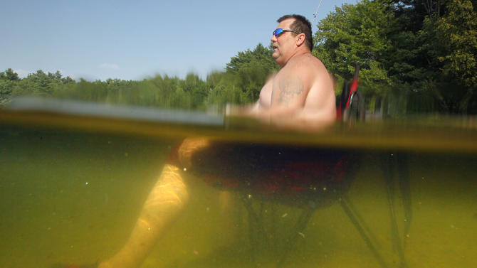 William Dyer, Jr., of Gortham, Maine stays cool seated on his beach chair waist-deep in Sabbathday Lake in New Gloucester, Maine, Thursday, July 21, 2011. The heat that has gripped much of the nation arrived in Maine on Friday. (AP Photo/Robert F. Bukaty)