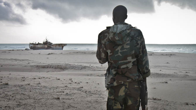 FILE - In this Sunday, Sept. 23, 2012 file photo, a Somali soldier looks out at a Taiwanese fishing vessel that washed up on shore after the pirates were paid a ransom and released the crew, in the once-bustling pirate den of Hobyo, Somalia. A U.K.-led Piracy Ransom Task Force says the shipping industry must adopt additional measures to ensure that payments aren't made to pirates after a successful attack. (AP Photo/Farah Abdi Warsameh, File)