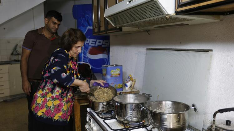 An Iraqi Christian woman from Mosul, who fled from violence in their country, cooks lunch for other displaced Iraqis at the Latin Patriarchate Church in Amman
