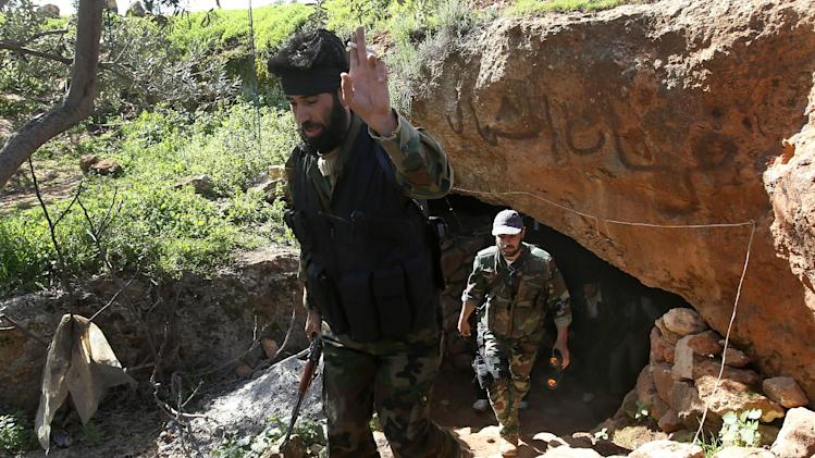"A Free Syrian Army fighter, Abu al-Yaman, left, a commander of Knights of the North brigade, cheers as he leaves with other rebels one of their caves to reconnaissance a Syrian army forces base of al-Karmid, at Jabal al-Zaweya, in Idlib province, Syria, Wednesday, Feb. 27, 2013. Syrian warplanes carried out airstrikes on rebels trying to storm a police academy outside Aleppo on Wednesday, while jihadi fighters battled government troops along a key supply road leading to the southeastern part of the city, activists said. The Arabic words in the cave entrance read:""Knights of the North brigade"". (AP Photo/Hussein Malla)"